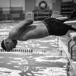 Alexey jumps in the water during a training in the swimming pool.